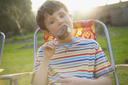 Portrait boy eating chocolate ice cream bar on summer patio