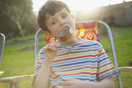 Portrait boy eating chocolate ice cream bar on summer patio