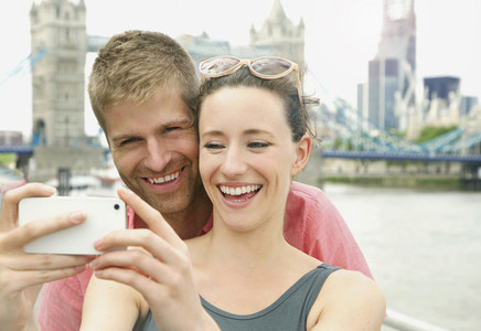 Happy couple taking selfie with camera phone in front of Tower Bridge