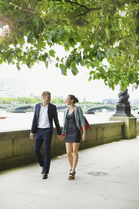 Happy young couple holding hands and walking along Thames River