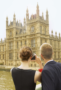 Young couple with camera photographing Houses of Parliament