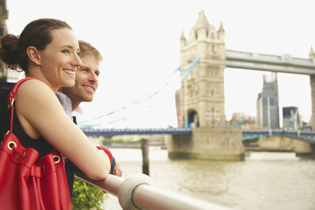 Happy young couple enjoying view of Thames River and Tower Bridge