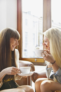 Happy young women drinking coffee in cafe window