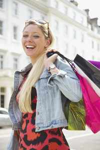 Portrait happy young woman with shopping bags on sunny urban street