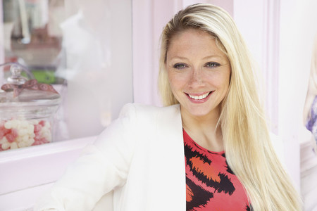 Portrait smiling young blonde woman outside bakery