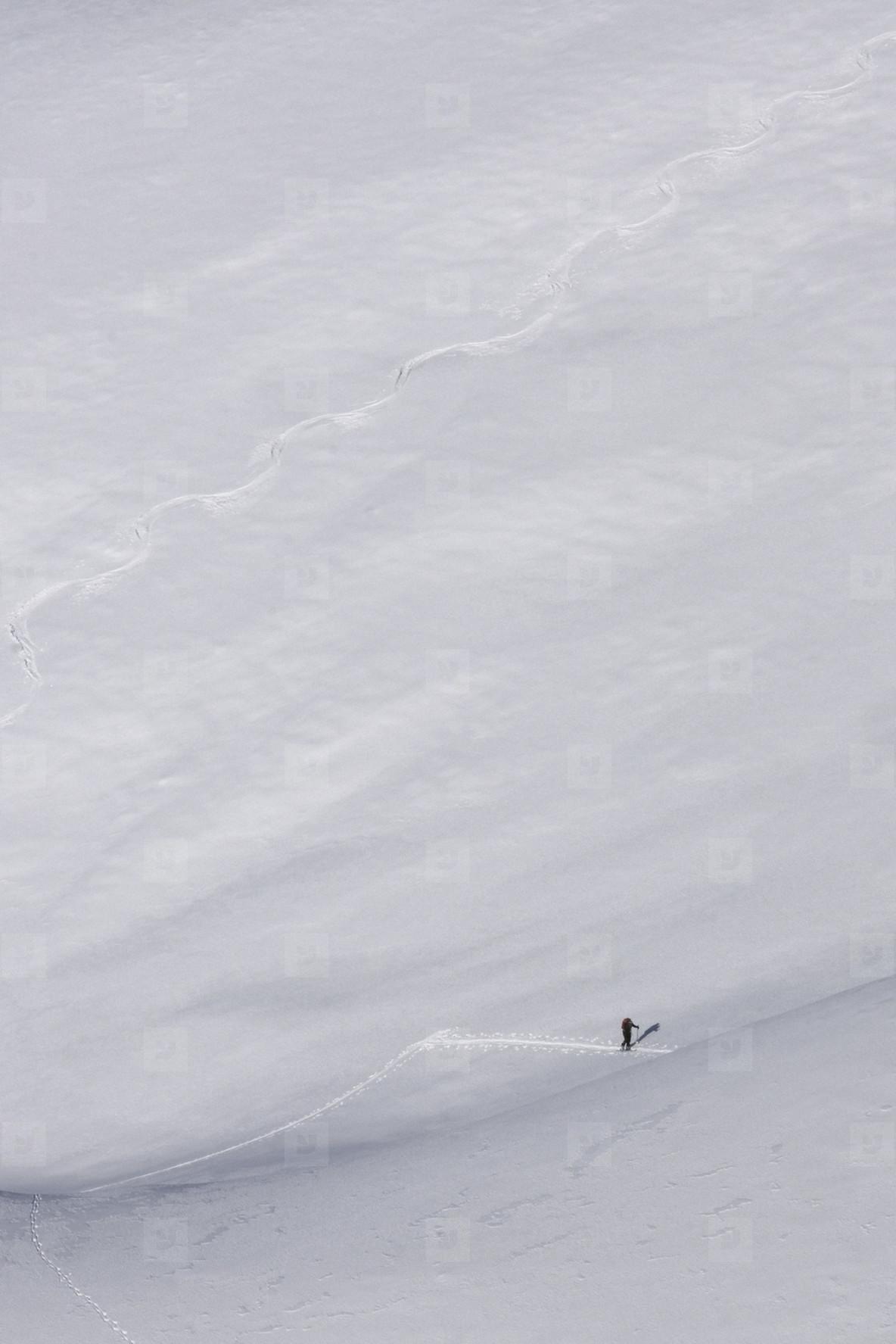 Distant hiker on steep mountain ski slope