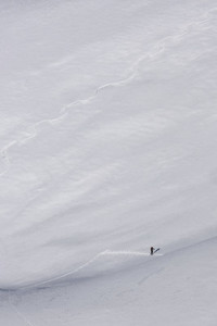 Distant hiker on steep mountain ski slope
