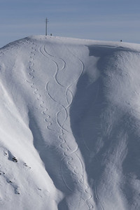 Downhill skiing tracks on sunny