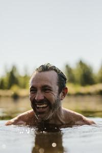 Smiling mature man swimming in a lake