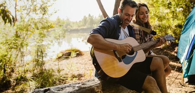 Beautiful couple enjoying camping by the lake