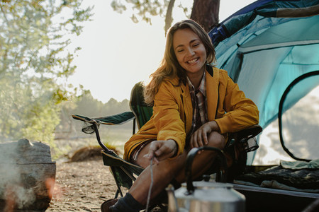 Smiling woman sitting at campsite