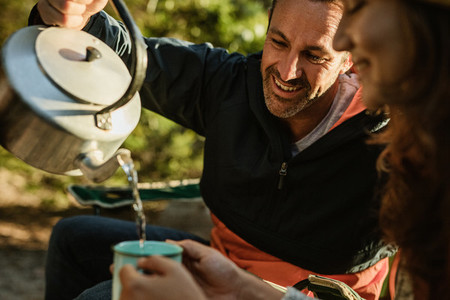 Couple having coffee at campsite