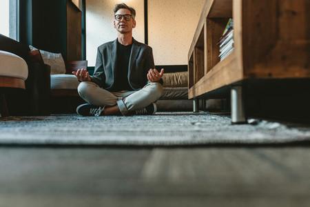 Mid adult businessman doing yoga meditation in office
