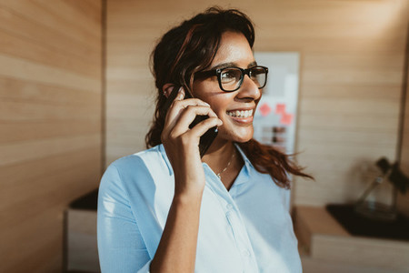 Woman in office talking on phone and smiling