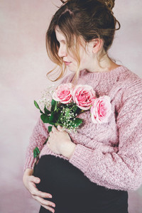 Young pregnant woman holding a bouquet of roses