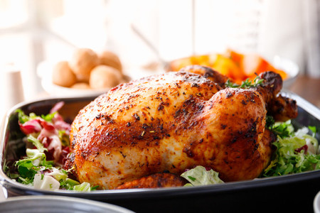 Whole roasted chicken with fresh salad in black dish