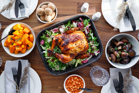 Top view of decorated festive table with whole roasted chicken salad pumpkin mushrooms beans and walnut The concept of family dinner or Thanksgiving celebrate