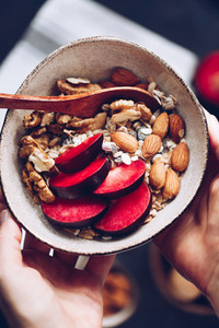 Hands hold a bowl of morning granola with almond and sliced plum  Healthy energy breakfast  top view