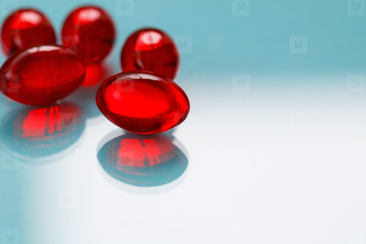 Close up of red painkiller pills on a blue background