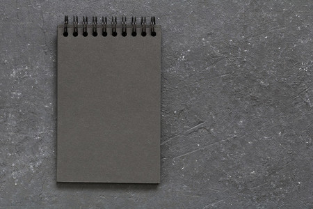 Top view on the blank page of black notepad on the black table Copy space