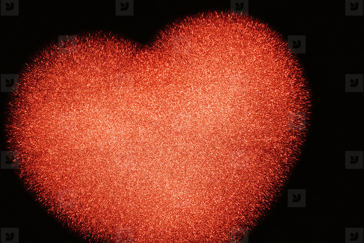 The background of a cropped red shiny heart on black
