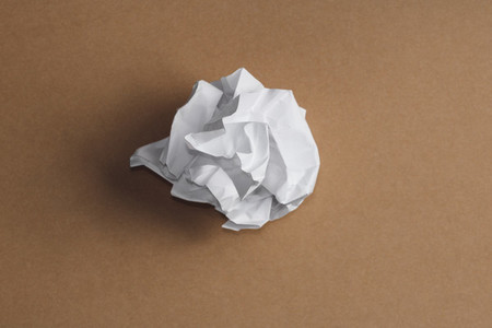 Top view of the ball of crumpled white paper on a kraft background