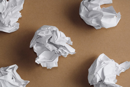 Top view of balls of crumpled white paper on a kraft background