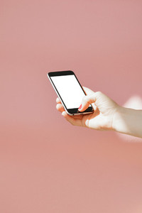 Hand holding mobile phone against the pink wall