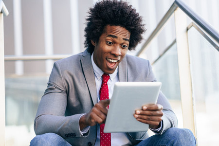 Black Businessman using a digital tablet sitting near an office building