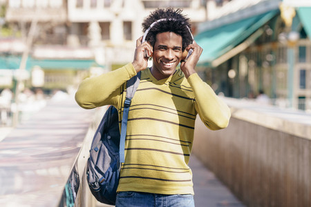 Black man listening to music with wireless headphones sightseeing in Granada