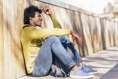Black man with afro hair and headphones resting on the ground