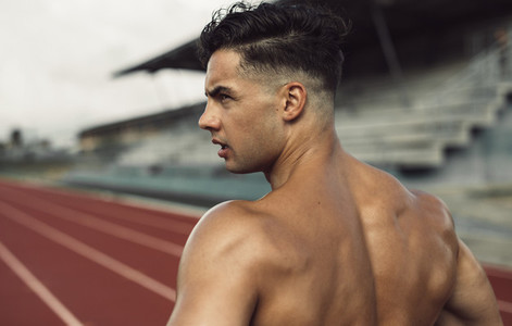 Healthy young man standing on track field