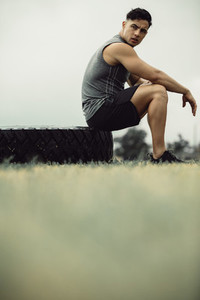 Muscular man resting after cross training outdoors