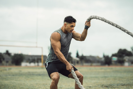 Strong man exercising with battle ropes on a field