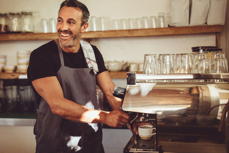 Smiling barista making espresso with a coffee maker