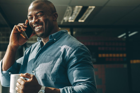 Smiling businessman with coffee talking on cellphone