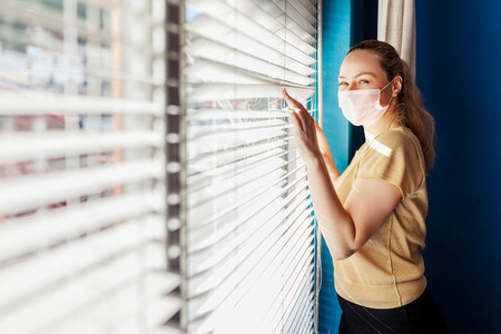 Woman looking out the blind window wearing a surgical mask