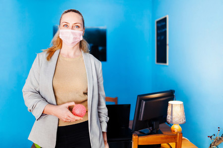 Woman wearing surgical mask with covid 19 model in her hand