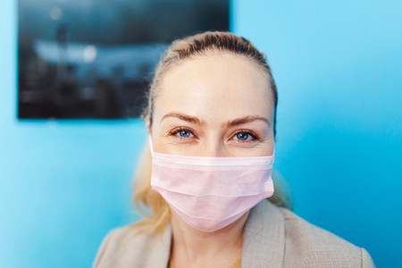 Woman wearing surgical mask with covid 19 maquette in her hand