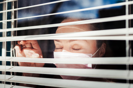 Woman with closed eyes wearing a surgical mask near a window