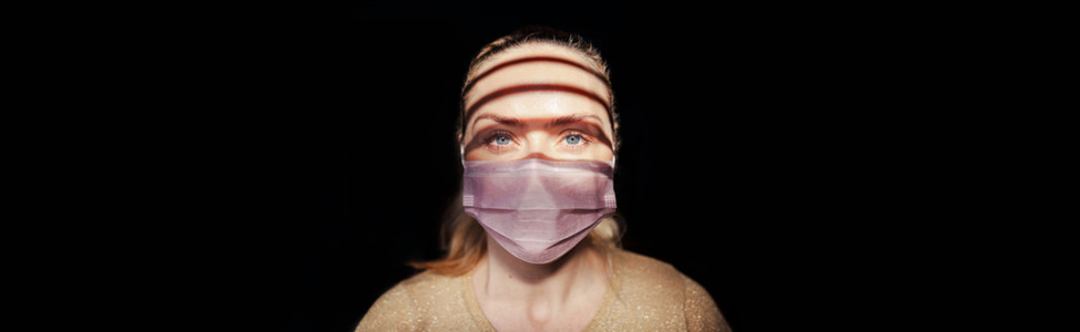 Woman wearing a surgical mask during quarantine in her house
