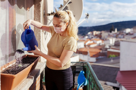 Woman watering during quarantine in her balcony