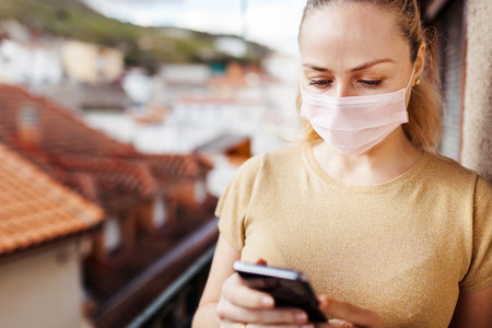 Woman using her smartphone during quarantine in her balcony