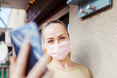 Woman taking a selfie during quarantine in her balcony