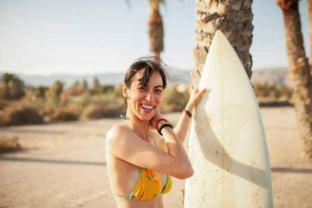 Young smiling woman walking through the beach with her surfboard