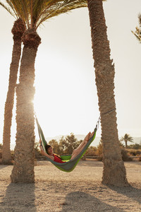 Young woman lying in his hammock among palm trees on the beach