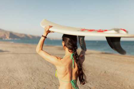 Young woman walking through the beach with her surfboard