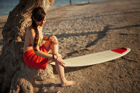 Young woman in the beach with her surf table waiting in the sand