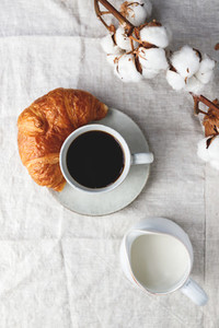 Cup of black coffee with croissant and milk on  table The concept of breakfast flat lay top view