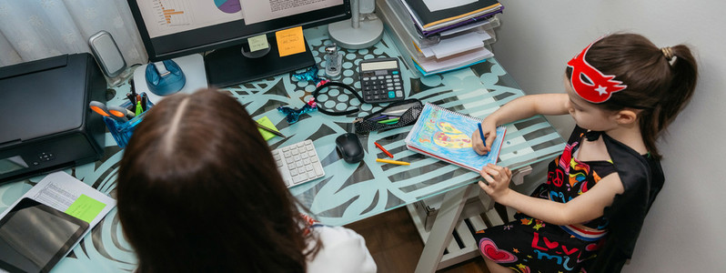 Woman teleworking with her daughter drawing